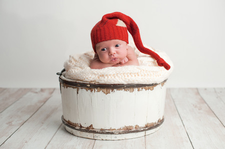 stocking cap: Portrait of a two week old, alert, newborn baby boy with a cute expression. He is posed in a white bucket with his chin on his hands and is wearing a red stocking cap. Stock Photo