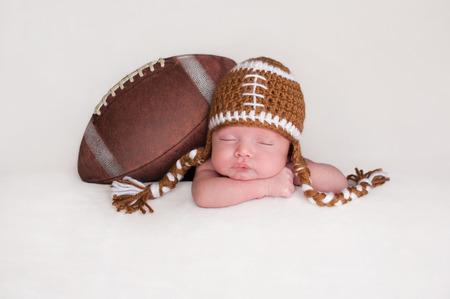recien nacido: Retrato de una, dormir beb� reci�n nacido dos semanas de edad. �l se plantea con un f�tbol americano que lleva un sombrero de f�tbol de ganchillo.