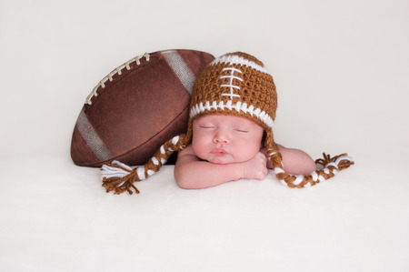 Portrait of a two week old, sleeping newborn baby boy. He is posed with an American football wearing a crocheted football hat.