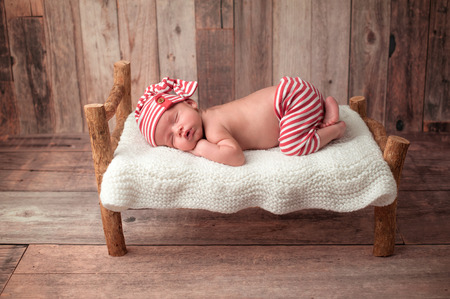 Portrait of a two week old newborn baby boy. He is sleeping on a miniature bed wearing red and white striped pajamas. Shot in the studio on a rustic wood background.