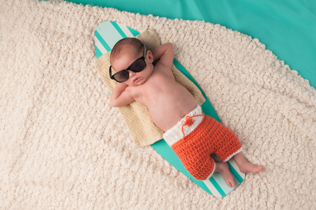 Newborn baby boy sleeping on a tiny surfboard. He is wearing black sunglasses and crocheted boardshorts.