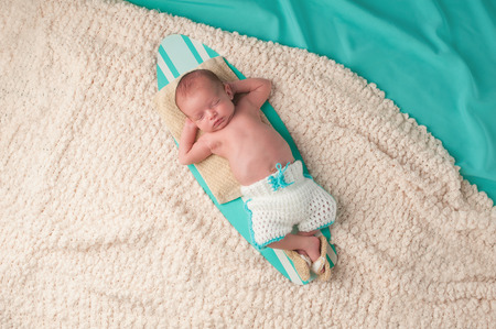 Newborn baby boy sleeping on a tiny surfboard. He is wearing crocheted boardshorts and sandals.