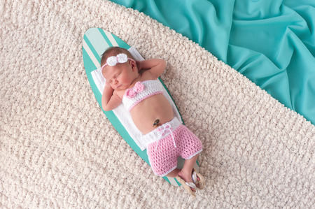 Nine day old newborn baby girl sleeping on a tiny surfboard. She is wearing pink and white crocheted boardshorts, bikini top and sandals.