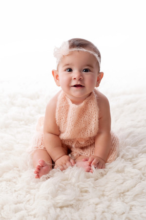 romper: A portrait of a happy, 6 month old baby girl wearing a peach colored, knitted mohair romper. She is sitting on a cream colored sheepskin rug. Stock Photo