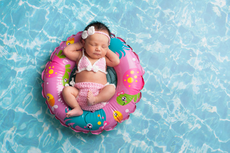 sleep baby: Nine day old newborn baby girl sleeping on a tiny inflatable swim ring. She is wearing a crocheted pink and white bikini.