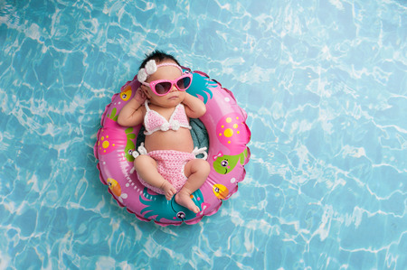 pink bikini: Nine day old newborn baby girl sleeping on a tiny inflatable swim ring. She is wearing a crocheted pink and white bikini and pink sunglasses.