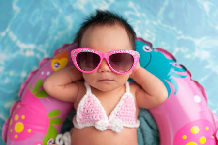 Nine day old newborn baby girl wearing pink sunglasses and a pink and white bikini. She is sleeping on a tiny inflatable swim ring. Standard-Bild