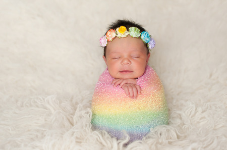swaddle: A sleeping nine day old newborn baby girl bundled up in a rainbow colored swaddle. She is propped up on a cream colored flokati (sheepskin) rug and wearing a crown made of roses.