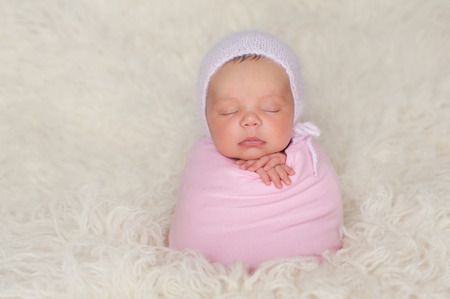 bonnet up: A sleeping nine day old newborn baby girl bundled up in a pink swaddle. She is propped up on a cream colored flokati (sheepskin) rug and wearing a knitted angora bonnet.