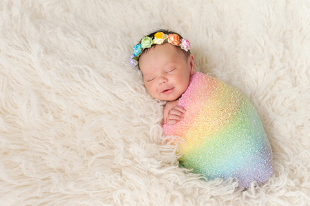 A smiling nine day old newborn baby girl bundled up in a rainbow colored swaddle. She is lying on a cream colored flokati (sheepskin) rug and wearing a crown made of roses.