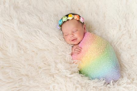Een glimlachende negen dagen oud pasgeboren baby meisje gebundeld in een regenboog gekleurde inbakeren. Ze ligt op een crèmekleurige flokati (schapenvacht) tapijt en het dragen van een kroon van rozen.