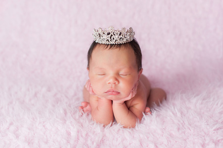 Portrait of nine day old sleeping newborn baby girl. She is wearing a rhinestone crown and is posed with her chin in her hands. Standard-Bild