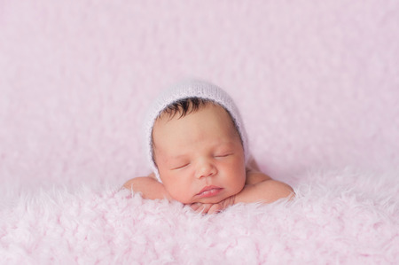 Portrait of nine day old sleeping newborn baby girl. She is wearing a knitted bonnet and is lying on a soft, fuzzy, pink blanket.