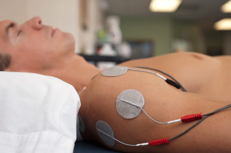 Physical therapy or chiropractic treatment of a male patients injured shoulder using transcutaneous interferential electrical stimulation (TENS) for pain management. Stock Photo