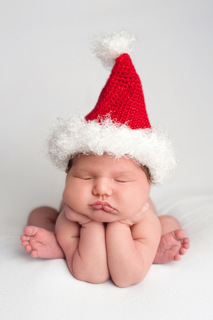 crocheted: A ten day old, newborn, baby girl wearing a crocheted Santa hat. She is posed with her hands under her chin and sleeping on a white fabric backdrop.