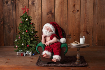 cute babies: Two week old, newborn, baby boy wearing a crocheted Santa suit with beard. Hes sleeping on an armchair. Shot in the studio with props, such as a Christmas tree, glass of milk and crocheted cookies. Stock Photo