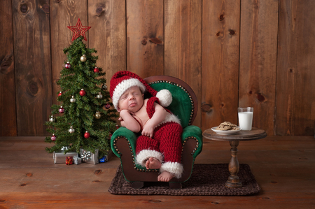 Two week old, newborn, baby boy wearing a crocheted Santa suit. He is sleeping on a tiny armchair. Shot in the studio with props, including a Christmas tree, glass of milk and crocheted cookies.