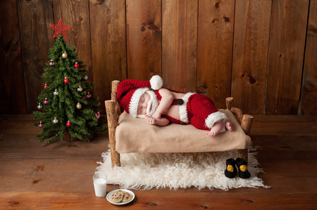 santa suit: Two week old, newborn, baby boy wearing a crocheted Santa suit and sleeping on a tiny, wooden bed. Shot in the studio with props, including a Christmas tree, glass of milk and crocheted cookies. Stock Photo