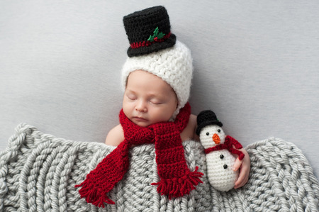 plush toy: Two week old, newborn, baby boy wearing a crocheted snowman bonnet and scarf. Hes holding a matching plush toy and sleeping on light gray fabric.
