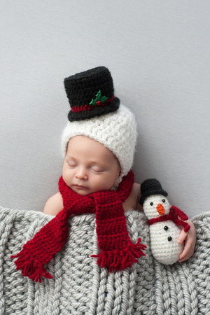 snug: Two week old, newborn, baby boy wearing a crocheted snowman bonnet and scarf. Hes holding a matching plush toy and sleeping on light gray fabric.