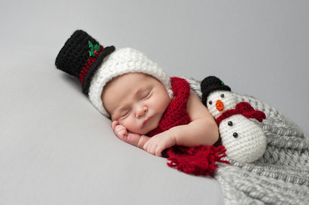 snug: Sleeping, two week old, newborn, baby boy wearing a crocheted snowman bonnet and scarf with matching plush toy.