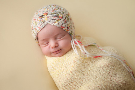 snug: A portrait of a beautiful, two week old, newborn baby girl wearing a crocheted bonnet. She is smiling and sleeping on yellow colored fabric.