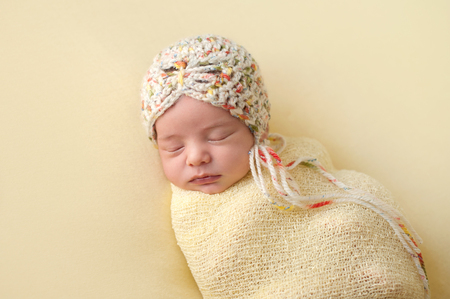 snug: A portrait of a beautiful, sleeping, two week old, newborn baby girl wearing a crocheted bonnet. She is swaddled with gauzy, yellow fabric.