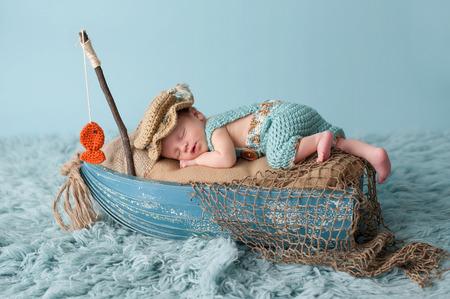 Portrait d'un garçon nouveau-né âgé de trois semaines. Il dort dans un bateau miniature et porte une salopette au crochet et un chapeau de pêcheur. Tourné en studio sur un tapis flokati de couleur aqua. Banque d'images