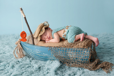 Portrait of a three week old newborn baby boy. He is sleeping in a miniature boat and wearing crocheted overalls and a fishermans hat. Shot in the studio on an aqua colored flokati rug.