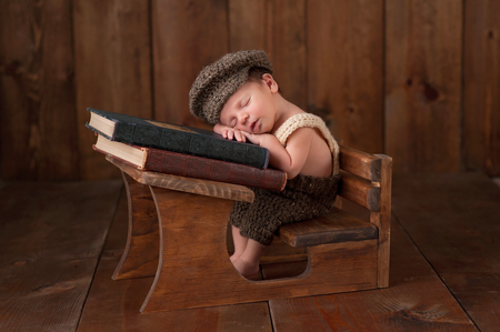 Three week old newborn baby boy wearing crocheted cap, shorts and suspenders. He is sitting at a tiny school desk and sleeping on a stack of vintage books.