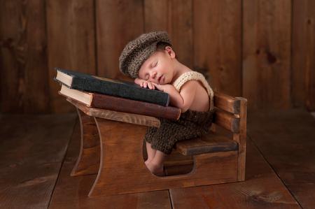 gente durmiendo: Tres semanas de edad bebé recién nacido que lleva el casquillo de punto, pantalones cortos y tirantes. Él está sentado en una pequeña mesa de la escuela y dormir en una pila de libros antiguos.