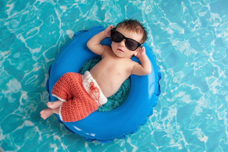 float tube: Three week old newborn baby boy sleeping on a tiny inflatable swim ring. He is wearing crocheted board shorts and black sunglasses.
