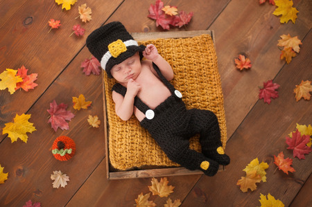 crocheted: Three week old newborn baby boy wearing a crocheted Pilgrim costume. He is sleeping in a wooden crate surrounded by fall colored leaves.