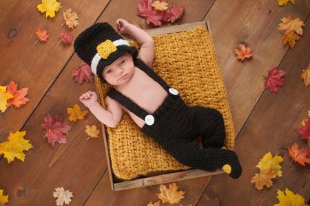 Three week old newborn baby boy wearing a crocheted Pilgrim costume. He is lying in a wooden crate surrounded by fall colored leaves.