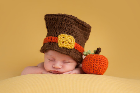 pilgrim costume: Three week old newborn baby boy wearing a crocheted Pilgrim hat. He is sleeping on a gold blanket next to a crocheted pumpkin.