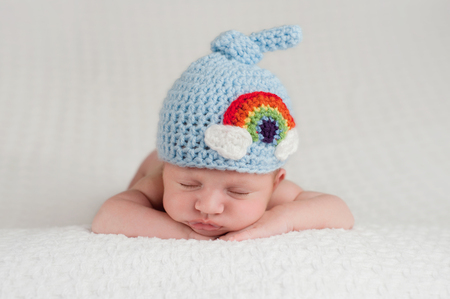 A sleeping, three week old, newborn baby boy wearing a top knot beanie with rainbow design. Shot in the studio on a white blanket. Archivio Fotografico
