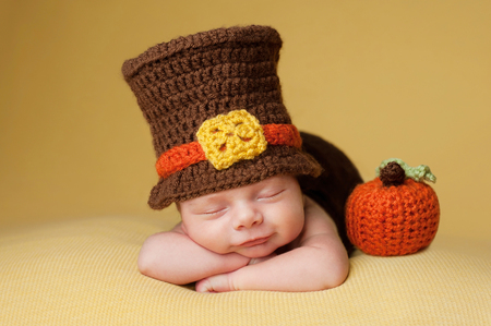 pilgrim costume: Smiling four week old newborn baby boy wearing a crocheted Pilgrim hat. He is sleeping on a gold blanket next to a crocheted pumpkin. Stock Photo