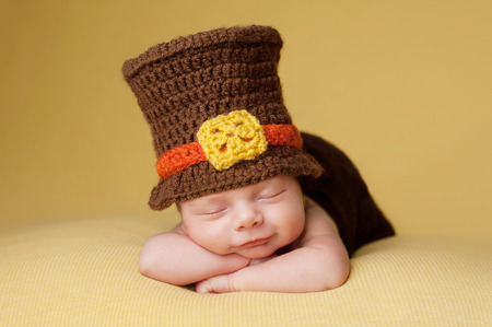 crocheted: Smiling four week old newborn baby boy wearing a crocheted Pilgrim hat and sleeping on a gold blanket.