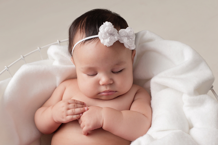 snug: Four month old baby girl wearing a white, bow headband. She is sleeping on white fabric placed inside of a wire basket. Shot in the studio on a beige background.