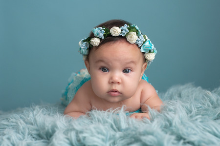 four month: Studio portrait of a four month old baby girl propped up on her forearms and wearing a turquoise colored floral crown.