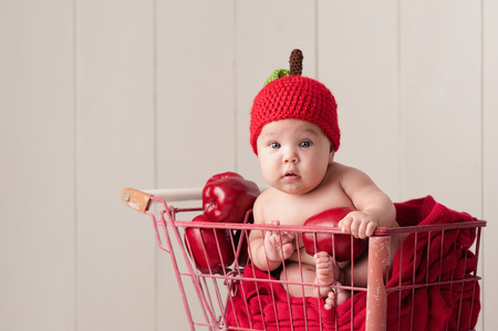 four month: A four month old baby girl wearing a crocheted, apple hat. She is sitting in a little, vintage shopping cart.