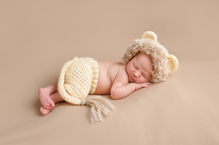 crocheted: A smiling three week old newborn baby boy wearing a crocheted lion costume. Shot in the studio on a khaki colored background.