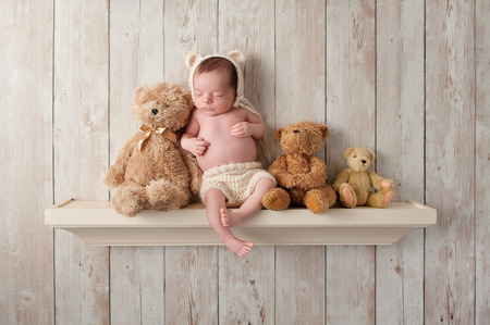 stuffed animals: Three week old newborn baby boy wearing a cream colored crocheted bear bonnet. He is sleeping on a shelf next to three Teddy Bears. Shot in the studio on a dark wood background. Stock Photo
