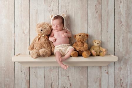 osos de peluche: Tres semanas de edad beb� reci�n nacido que lleva un capo oso de ganchillo color crema. �l est� durmiendo en un estante junto a tres osos de peluche. Un disparo en el estudio sobre un fondo de madera oscura.
