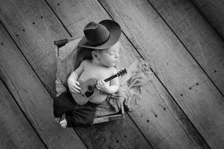 pequeño: Una imagen de B & W de un bebé tres semanas de edad que llevaba un sombrero de vaquero y jeans y tocando una pequeña guitarra acústica. Que se ha quedado en una caja de madera forrada con arpillera. Un disparo en el estudio en un fondo rústico de madera.