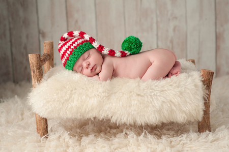 stocking cap: Three week old newborn baby boy wearing a red, white and green Christmas elf stocking cap. He is sleeping on a rustic wooden bed thats covered with a cream colored sheepskin.