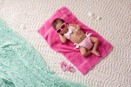 4 週齢の新生児の女の子ピンクのタオルの上に寝ています。かぎ針編みのピンクと白のビキニ、ピンクのサングラスを着ています。彼女はビーチでか 写真素材