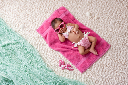 Four week old newborn baby girl sleeping on a pink towel. She is wearing a crocheted pink and white bikini and pink sunglasses. Shot in the studio with props made to look as if shes at a beach. Stock Photo