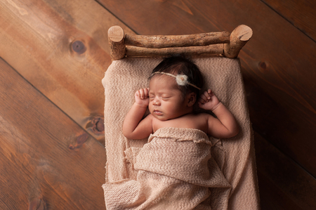 hispanic girl: Overhead shot of a four week old newborn baby girl sleeping on a tiny, rustic wooden bed. Shot in the studio on a wood background.