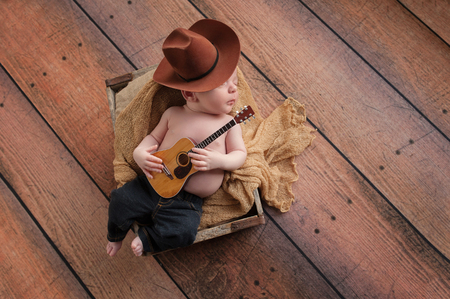 cowboy background: A three week old baby boy wearing a cowboy hat and jeans and playing a tiny acoustic guitar. He is lying in a wooden crate lined with burlap. Shot in the studio on a rustic, wood background.